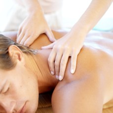 Masseuse Massaging Young Man Lying on Table Closed Eyes --- Image by © Royalty-Free/Corbis