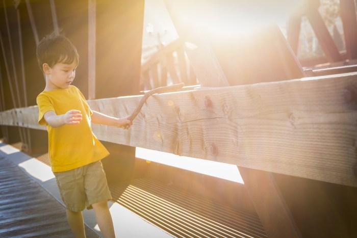 Handsome Mixed Race Boy Walking on Bridge Outdoors.