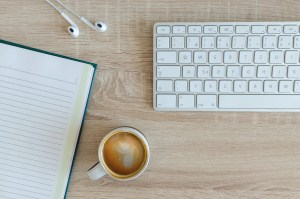 a coffee and keyboard on a desk perfect for writing vegan guest posts