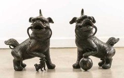 two similar sculptures of ancient Shih Tzu dogs
