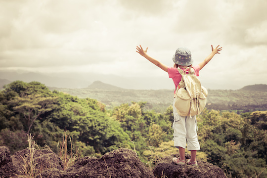 little girl with a backpack standing on a mountain top