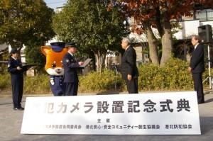 12月12日に新吉田第一公園(新吉田東6)にて行われた「防犯カメラ設置記念式典」で表彰される発起人の畠山英治(えいじ)さん(写真中央)、篠沢秀夫さん(同右)。表彰状を手にするのは陶山和美(すやまかずよし)港北警察署長