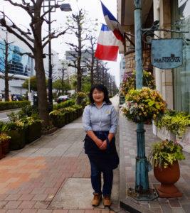 HANZOYAグループの屋外緑化を担当する嶋崎有紀恵さん。メンバー4人の中心となって活躍している。フランス料理HANZOYAは横浜アリーナ(左)に面した場所に立地している