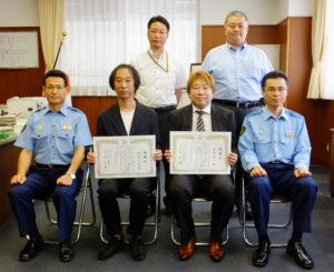 港北警察署の牧智明署長(前列左)、鈴木純一副署長(同右)らと記念撮影。生活安全課の箕輪裕治課長(奥左)は「2人の声かけこそが詐欺を防いだ」とその勇気を称(たた)える