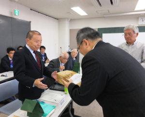 港北防犯協会の川島武俊会長(右)、港北警察署にこの10月から着任した生活安全課の鎌倉清課長(手前)から、13地区の各連合町内会長にネックストラップが配布された