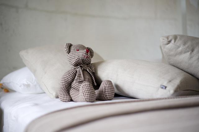 ベッドと枕とクマのぬいぐるみ