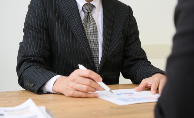 資料を使い説明するビジネスマン