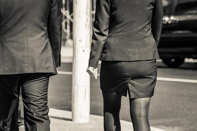 スーツ姿で歩く男女の後ろ姿