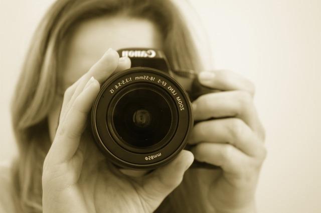 カメラのレンズを向ける女性