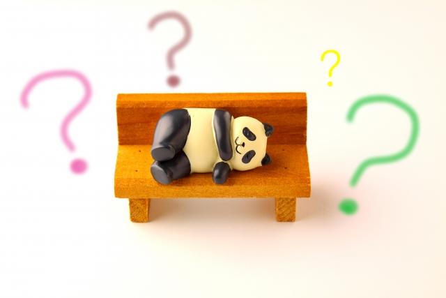 ベンチに寝て考えているパンダの人形