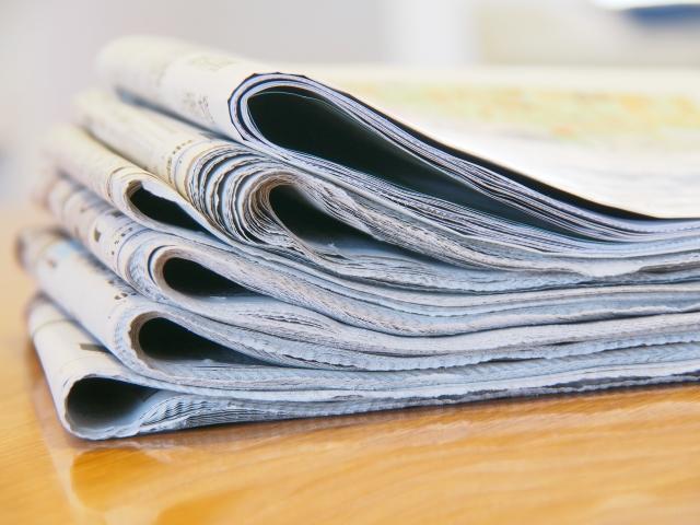 机の上に積まれた新聞紙