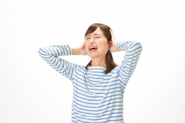 ショックを受け頭を抱える女性