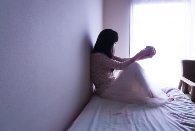 ベッドに座り考え込む女性