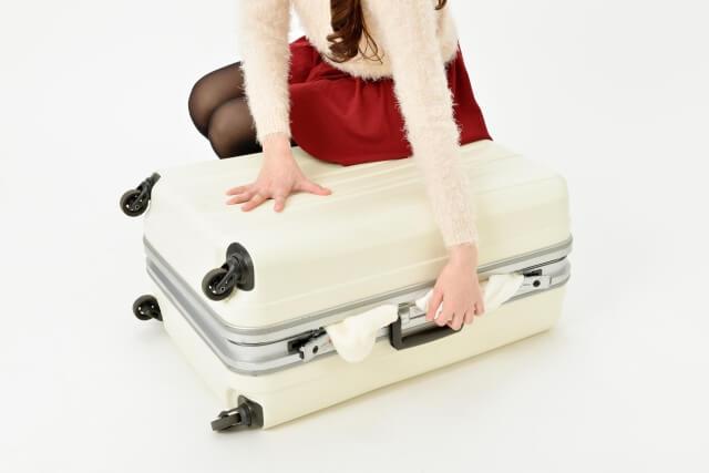 キャリーバッグに荷物を詰める女性