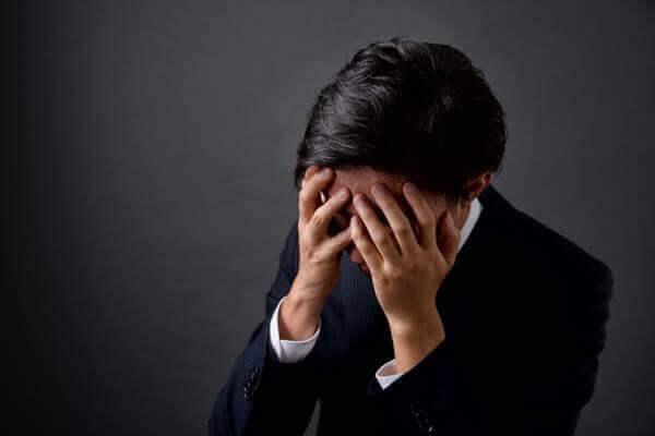 仕事で悩み頭を抱えるビジネスマン