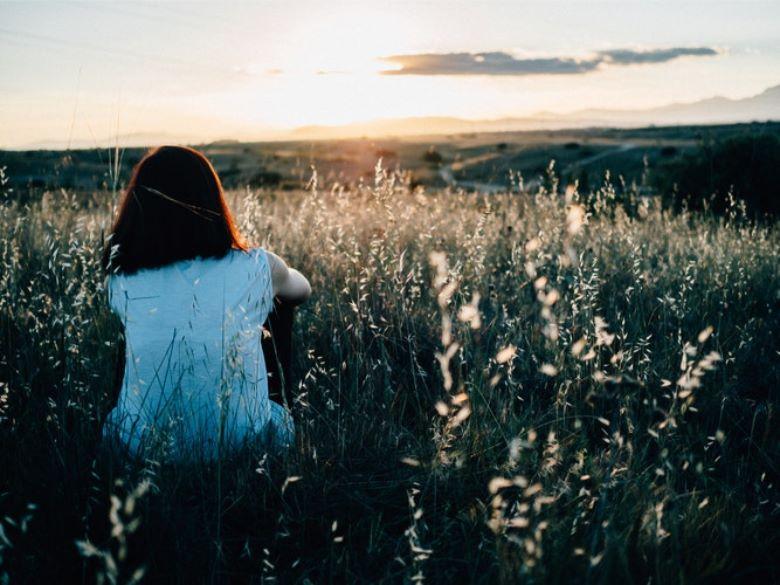 夕暮れに草原に座る人