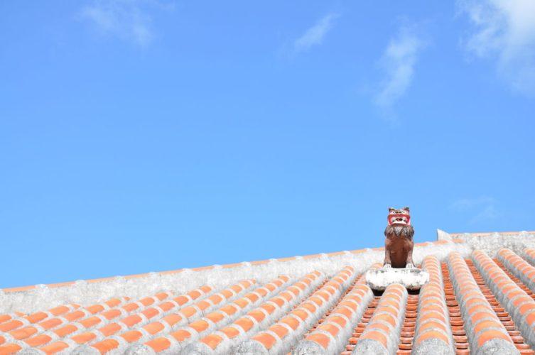竹富島の青空と赤瓦の屋根に立つシーサー