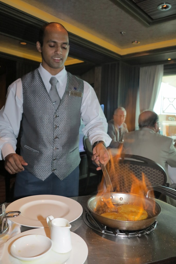 Fire whisk: A waiter prepares flambéed pineapple