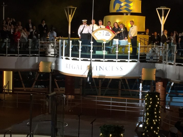 With the Love Boat cast looking on, the bottle hits the Regal Princess sign. It took another go to break it.
