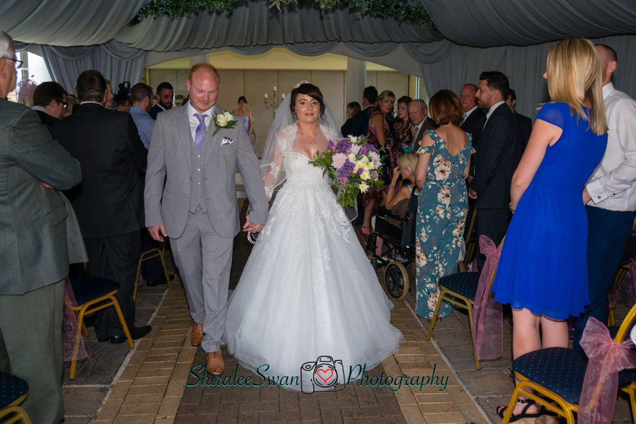 The new Mr & Mrs walk hand in hand for the first time at Friern Manor
