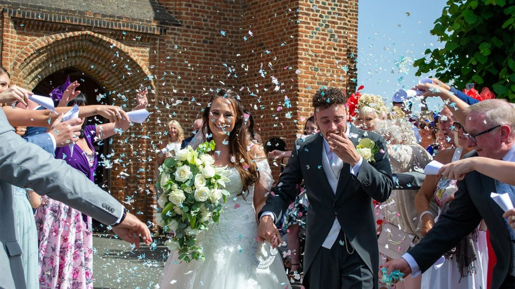 As the Bride and Groom walk from the church their guest stans along the path and throw confetti over the couple