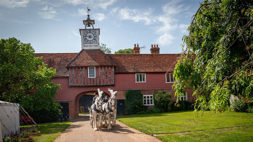 The Bride and Groom arrive at Ingatestone Hall in a carriage pulled by two white shire horses with the clock tower in the background and the marquee on the lawn to the right