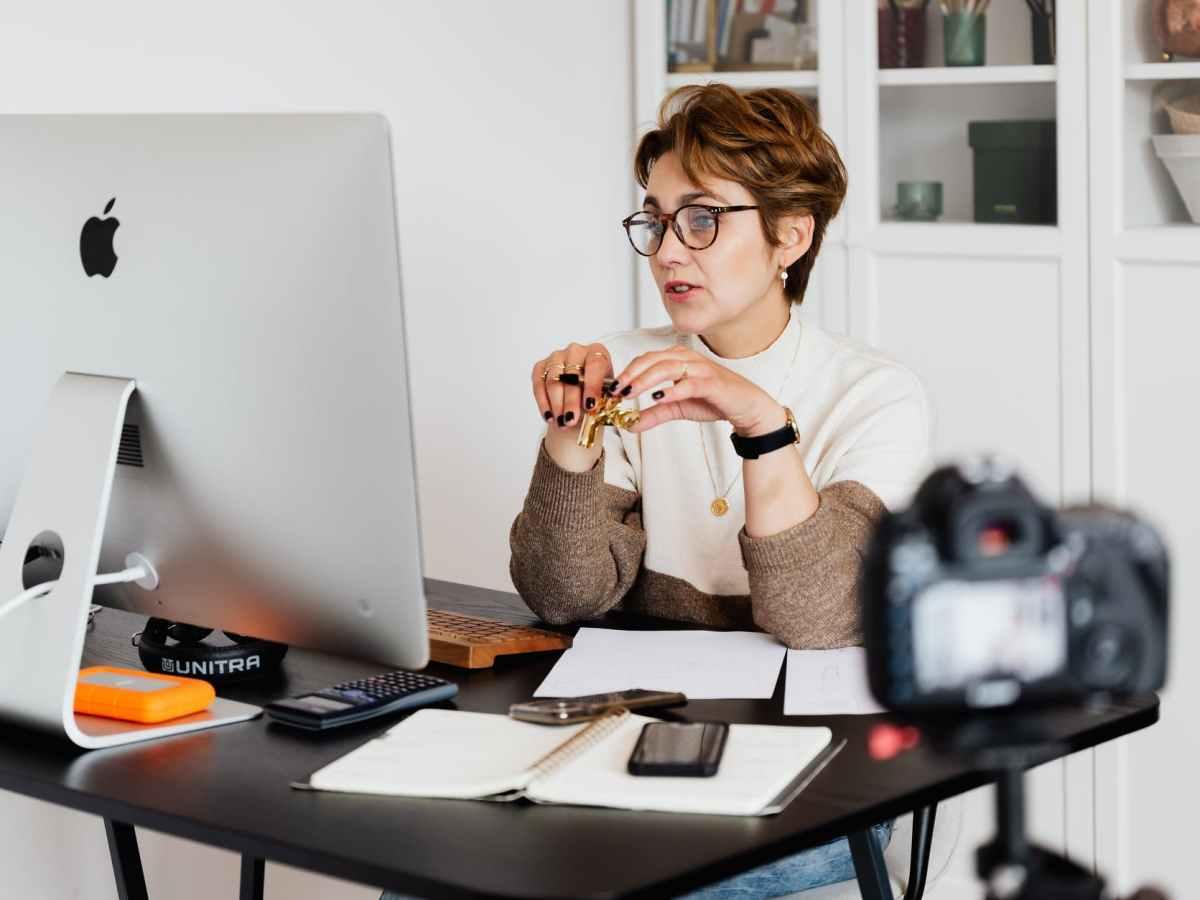 confident elegant lady in eyeglasses hosting webinar