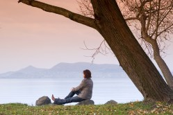 A young woman / lady is sitting and have a relax under a tree