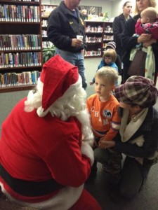 Santa kneeling to talk to young Sam and his mother