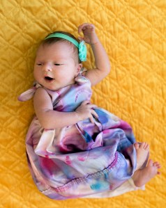 The almost-smile of a newborn. The dress was made from a pillowcase and hand dyed by Kate.