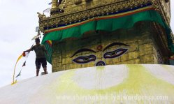 Man sprinkling the colourful water over the white massive dome of Swoyambunath.