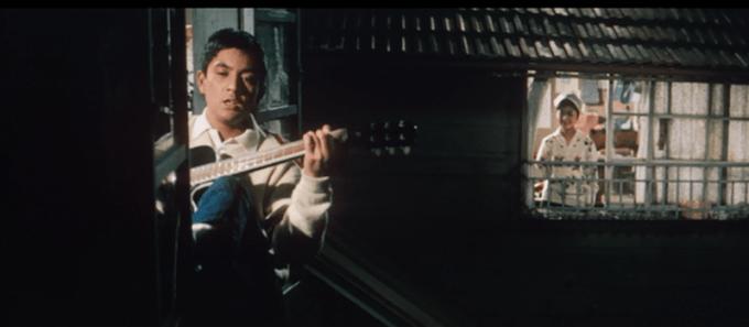 夜、住み込みの部屋でギターを弾いて歌っている