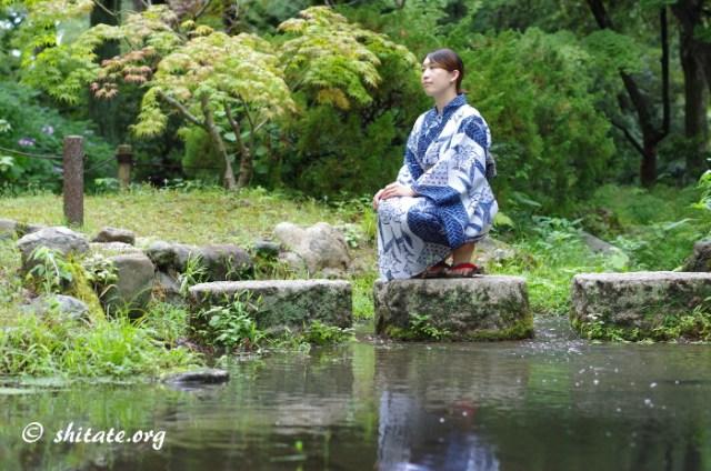 飛び石に座る紺の浴衣女性