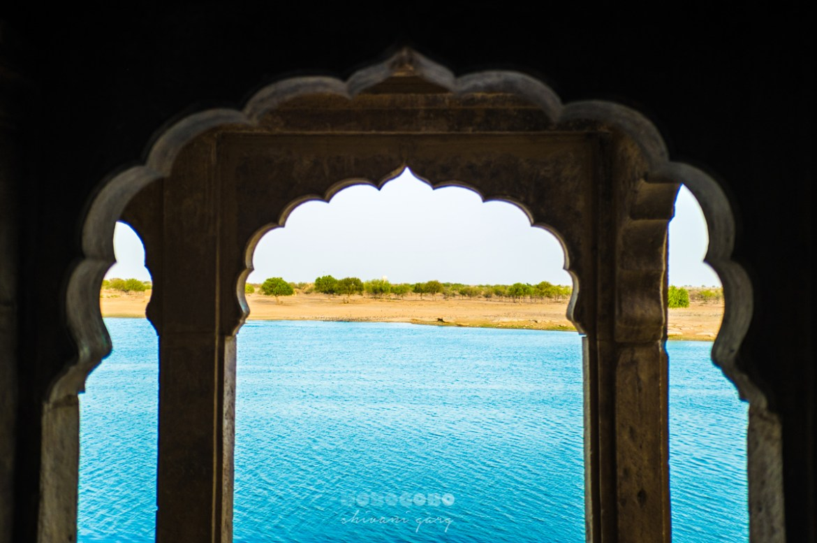 view of gadisar sagar lake from a rajasthani jharokha