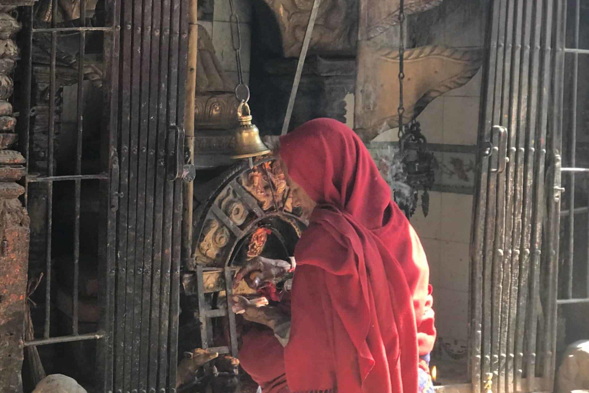 Woman praying before Shrine in Patan, Nepal