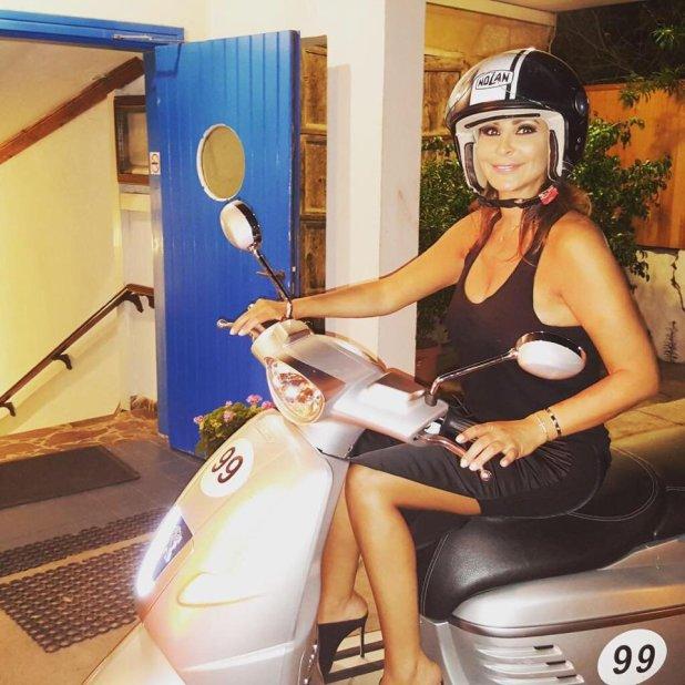 إليسا بفستان أسود قصير على دراجة نارية