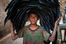 A child labour carrying leather to a van.