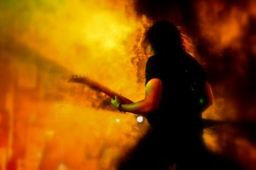 Oni, a guitarist from the band Warfaze plays under fiery light on a stage show in Dhaka, Bangladesh.