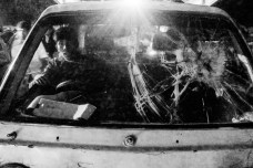 A driver of a Leguna(local pickup trucks, carrying people) seen through the broken windshield.