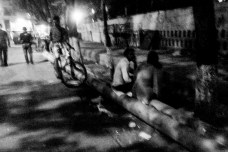 A couple sitting on abandoned poles near the pavement opposite of the college campus.