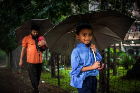 A little boy on his way back from school with his father.