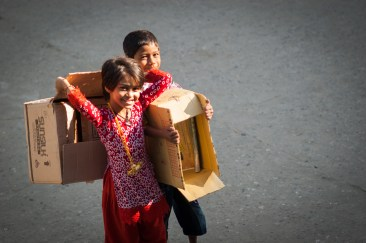 Kids carrying empty boxes to their homes.