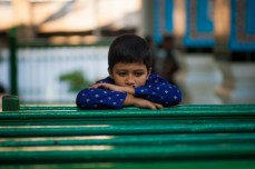 A kid in contemplation in the veranda as his parents prays inside the main hall.