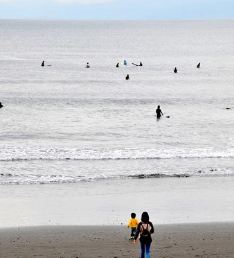 午後の片瀬西浜でサーファーと親子