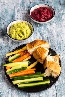 Avocado-Hummus, rote-Bete-Hummus, Fladenbrot, Gemüsesticks (gelbe und orangene Karotte, Gurke), Studio