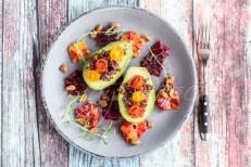 aufgeschnittene Avocado, mit rotem Bulgur gefüllt. Tomaten, Blutorange, kandierte Erdnüsse, Rosmarin, Studio