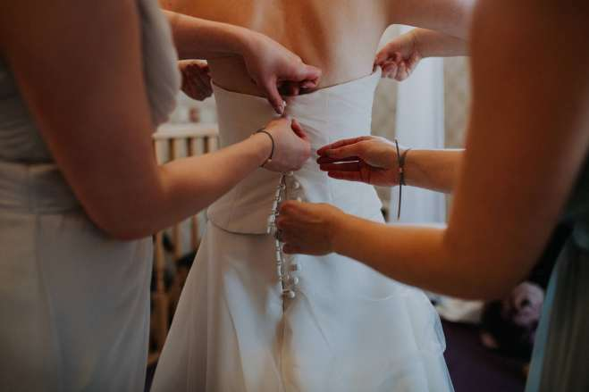 Bride putting on her wedding dress at Bassmead Manor Barn