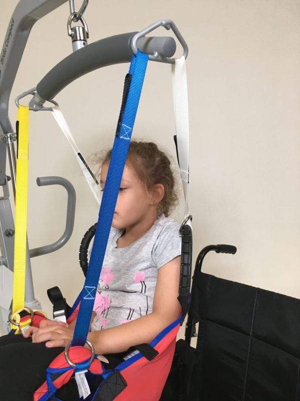 Young disabled girl being moved in ProMove sling with yellow and blue straps attached to the hoist