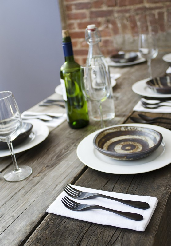 Image is a photograph of a stylish weathered-wood dining table laid with wine glasses, earthenware pottery and matt black finish Knork cutlery