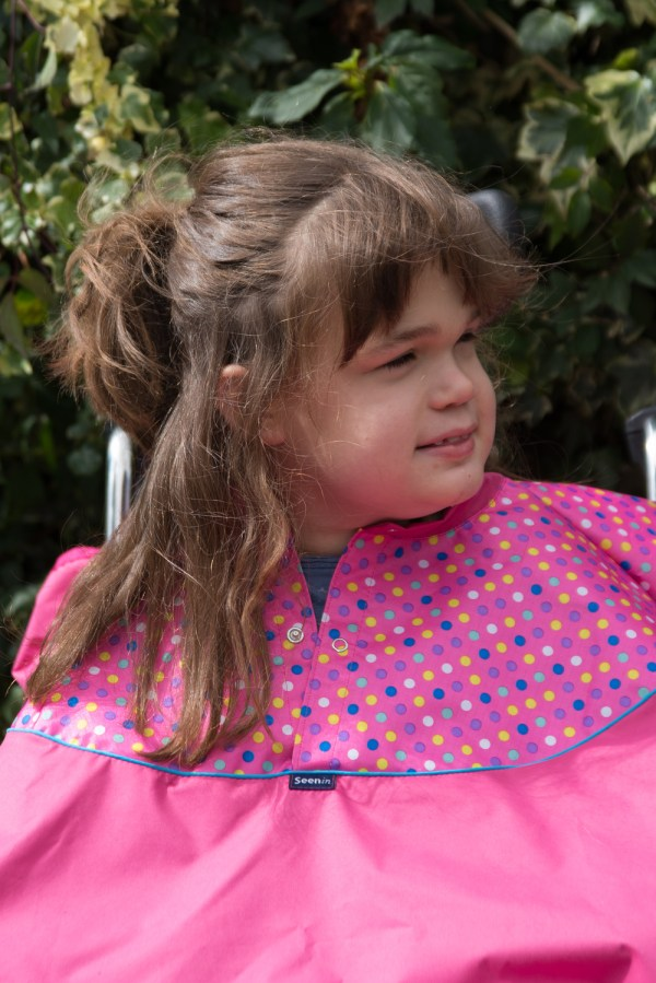 Disabled girl in fuchsia Seenin total waterproof wheelchair cover with spot pattern